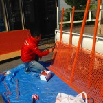 オレンジの上着を着た小笠原さんがパネルをオレンジに塗装しています^^