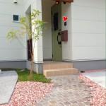 レンガや砕石をやさしい色でまとめて、グリーンのドアが引き立っています!
