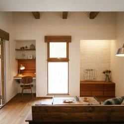 木製サッシがナチュラル感をアップさせる家。ちょっと吹抜けをつくったリビングの窓からは緑が見えてくつろげる空間に。