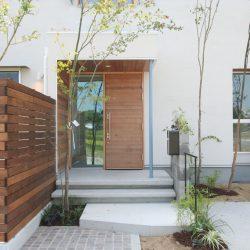 緑がゆれるエクステリア。オーダー木製玄関ドアも外観のシンプルかわいいお家に合わせてデザインしました。