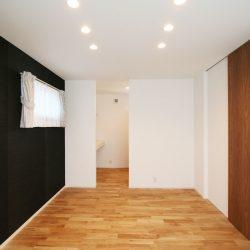 天井までのハイドアと黒のアクセントウォールでシンプルスタイリッシュなコーディネート。