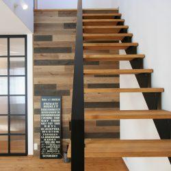 カッコいいアイアン階段に合わせて、黒系の色違いの板を貼り合わせた壁。男前空間です。