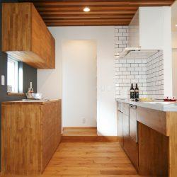 キッチンの空間だけは奥さまの特別な空間。天井をちょっと低めにアクセントに板を貼って、床は一段下げて食卓に座る家族と目線が合うように。