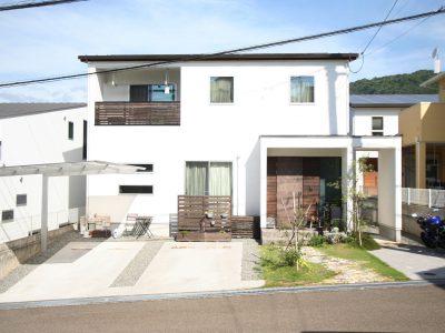 真っ白い塗り壁に、木製玄関ドアがかっこよく映えるシンプルな外観のFさま邸。